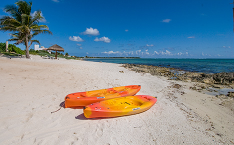sea kayaks on the beach at casa caribena vacation rental villa on tankah bay