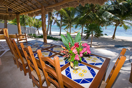 Dine on the beachfront patio overlooking the ocean at Casa Rosa vacation rental villa on Tankah Bay